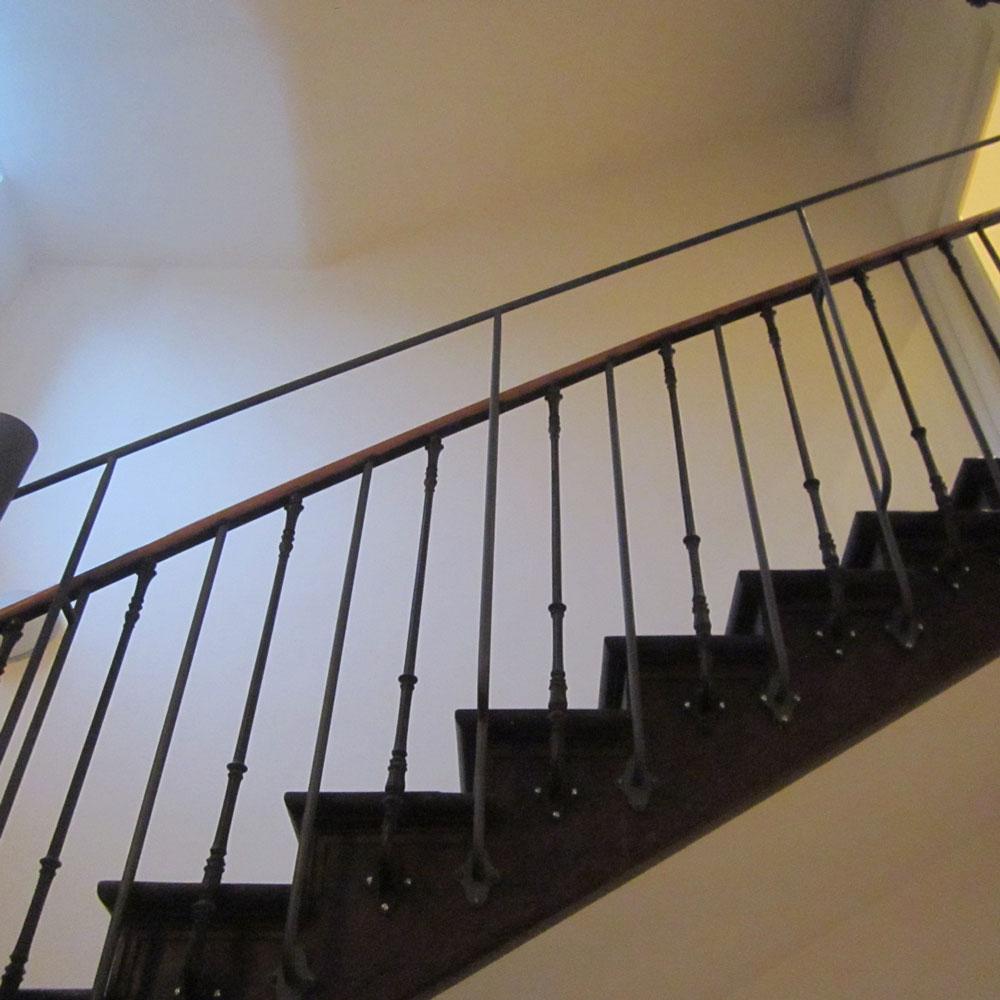 dunkle treppe mit holzgeländer, perspektive von unten.