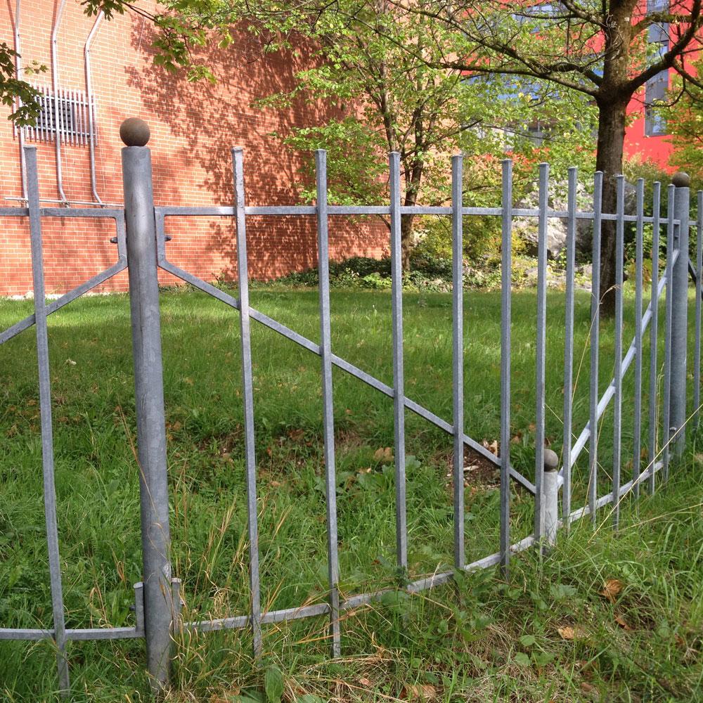 grauer zaun mit wiese drunter.
